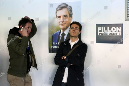 Two journalists react after learning that their interview with Valerie Boyer had been cancelled at the headquarters of French presidential hopeful Francois Fillon in Paris, France, . French voters are casting ballots for their next president in an unusually close first-round election Sunday, after a campaign dominated by concerns about jobs and immigration and clouded by security fears following a recent attack on police guarding the Champs-Elysees in Paris