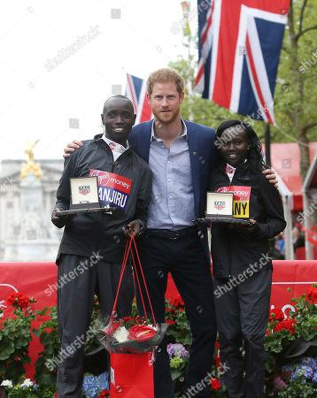 Britain's Prince Harry, center, poses with first place winners of the London Marathon, Kenya's Daniel Wanjiru, left, and Kenya's Mary Keitany in London, . Keitany broke Paula Radcliffe's women-only marathon world record