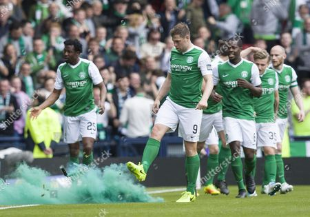 Grant Holt of Hibernian kicks a smoke bomb off the pitch after Dylan McGeouch scored to equalise 2-2 during the William Hill Scottish Cup semi-final tie between Hibernian & Aberdeen played at Hampden Park, Glasgow on 21st April
