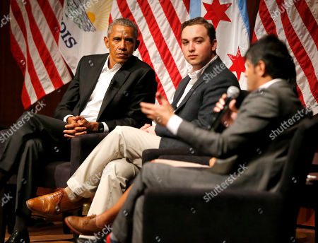 Former President Barack Obama and Max Freedman, center, listen to Harish Patel speaks during a conversation on civic engagement and community organizing, at the University of Chicago in Chicago. It's the former president's first public event of his post-presidential life in the place where he started his political career