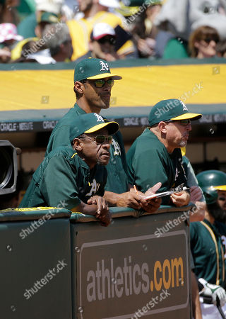 Oakland Athletics assistant Rickey Henderson, foreground, watches a baseball game between the Athletics and the Texas Rangers in Oakland, Calif