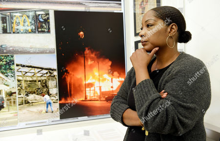 """Katynja McCory, lead docent for the """"Re-Imagine Justice"""" art exhibit, looks at L.A. Riots photos featured in the exhibit at the Community Coalition, in Los Angeles. When she thinks back to what she recalls of the Rodney King riots, McCory concludes she had been living in a bubble called childhood innocence. It was one that was forever shattered on that day her mother told the 13-year-old to get on the floor of their home and stay there, lest she be hit by a stray bullet"""
