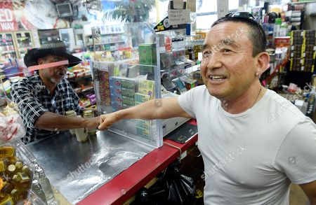 "James Oh, right, owner of Tom's Liquors, bumps fists with a customer at his store at the intersection of Florence and Normandie, in Los Angeles. ""At the time I think there was a lack of communication with the community,"" Oh says, discussing the 1992 uprising as hip-hop from a radio station blares over the store's intercom. ""But right now I'm telling you I've changed it here. I have great communication with people and here it's just safe as ever"