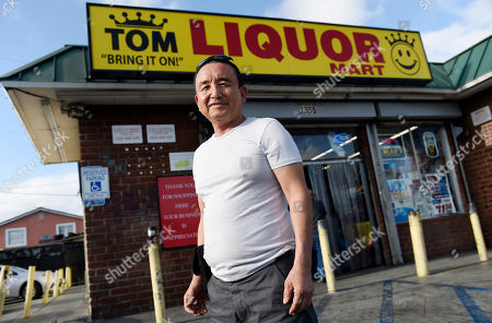 James Oh, owner of Tom's Liquors, poses outside his store at the intersection of Florence and Normandie, in Los Angeles. Most of those groceries weren't there when he took the place over, Oh says, so he moved out some of the booze to make room (although there's still plenty available) and brought in necessities like milk, eggs, sugar and an array of spices and sauces favored by Latino and African-American customers
