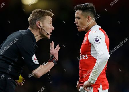 Arsenal's Alexis Sanchez is spoken to by referee Mike Jones after he was shown a yellow card during the English Premier League soccer match between Arsenal and Leicester City at the Emirates Stadium in London