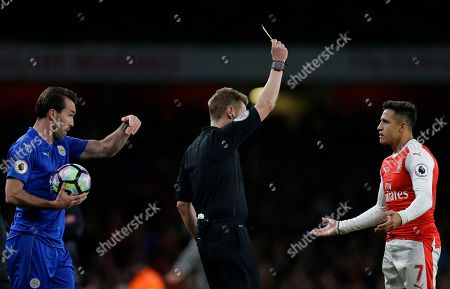 Referee Mike Jones show Arsenal's Alexis Sanchez a yellow card following an incident over a throw-in, during the English Premier League soccer match between Arsenal and Leicester City at the Emirates Stadium in London
