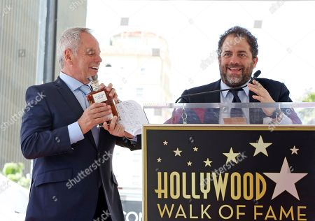 Wolfgang Puck, Brett Ratner Director Brett Ratner hands celebrity chef Wolfgang Puck a bottle of The Hilhaven Lodge whiskey at a ceremony honoring Puck with a star on the Hollywood Walk of Fame, in Los Angeles