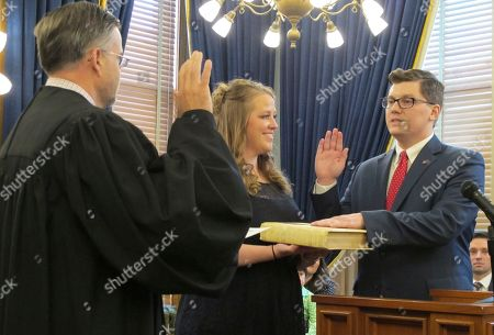 Former Kansas state Senator Jake LaTurner, right, takes the oath of office as state treasurer from Kansas Supreme Court Justice Caleb Stegall, left, as his wife, Suzanne, center, watches, at the Statehouse in Topeka, Kan. LaTurner, R-Pittsburg, is replacing former Treasurer Ron Estes after Estes won a special congressional election