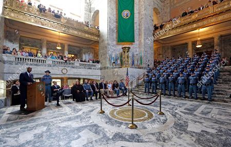 Washington State Patrol Chief John Batiste, left, speaks during the Washington State Patrol Academy graduation ceremonies in the Capitol rotunda, in Olympia, Wash. The 49 graduates, standing right, of the 107th Trooper Basic Training Class went through nearly six months of field and academy training, and were given the oath of office by Washington State Supreme Court Justice XXXX