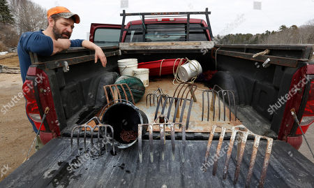 Dan Harrington pauses at his truck after a day of scouting mudflats in search of bloodworm, in Freeport, Maine. Harrington digs for marine worms using rakes with tines of various lengths and widths, depending on the mud's firmness