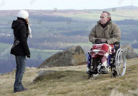 'Emmerdale'   TV   Soap   -   2008 Pictured: David and Miles hear from Carl that Donald has gone out for the day with Nicola. Miles is taken by David's alarm and demands to know what's going on. David fills him in that Nicola is trying to kill Donald. At the top of the cliff, Nicola surveys the terrain, steeling herself for what she needs to do. Donald asks her to wheel him closer to the edge stating that he wants to make things easier for her.  Nicola De Souza [Nicola Wheeler], Donald De Souza [Michael Jayston]