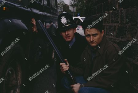 As Joe becomes suspicious when he finds the Post Office closed and a man sitting in a car outside with the engine running, Michael goes to call the police from Victoria Cottage and they cordon off the area - With Michael Feldmann, as played by Matthew Vaughan. (Ep 1871 - 24th May 1994).