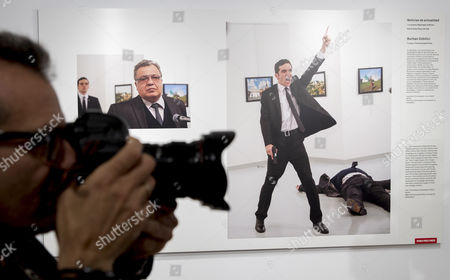 Stock Picture of A photographer stands in front of the 2017 World Press Photo of the Year winning image by Associated Press' Turkish photographer Burhan Ozbilici depicting Mevlut Mert Altintas after shooting Andrei Karlov(R), the Russian ambassador to Turkey, at an art gallery in Ankara (Turkey), during the inauguration of the World Press Photo Exhibition 2017 at the Cajasol Foundation center in Seville, southern Spain, 27 April 2017. The exhibition features a hundred of images awarded with the World Press Photo and will be open to the public until the upcoming 18 May.