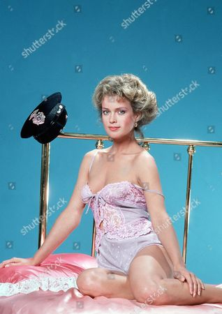'Policewoman Centerfold' TV - 1983 -  Jennifer Oaks (Melody Anderson) poses on a bed, her police hat hangs from the bed post.