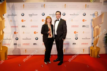 German script author and director of 'Toni Erdmann' Maren Ade poses with her trophy next to actor Bastian Pastewka (R) in the press room at the 67th German Film Awards in the Palais venue am Funkturm in Berlin, Germany, 28 April 2017. The Lola awards are presented in 18 categories.
