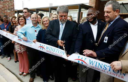 Flanked by the center's employees, Paul Black, CEO of the Winston Medical Center, cuts the celebratory ribbon during the grand opening of the rebuilt medical center in Louisville, Miss., . The medical facility and neighboring nursing home were heavily damaged by an EF4 tornado, that tore through the community leaving hundreds homeless and 10 dead three years ago. The community celebrated the new $55 million medical campus and nursing home built on the sites of the destroyed facilities, which will be open for patients May 1, 2017