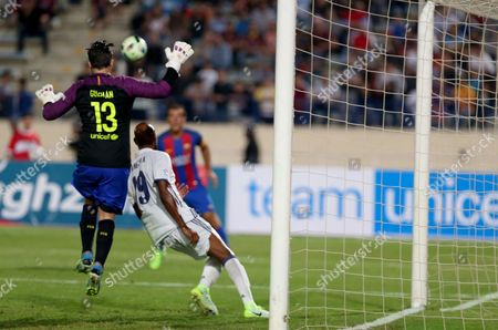 Stock Picture of Barcelona keeper Guzman (C) fights for the ball with player of Real Madrid  Nicolas Anelka (L) during a friendly Football Game Of Legends El Classico: Real Madrid vs Barcelona at Camille Chamoun stadium in Beirut, Lebanon, 28 April  2016.