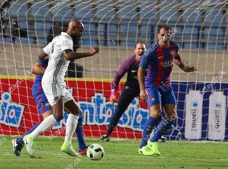 A Barcelona player (R) defends  Real Madrid's Nicolas Anelka (L)  during a friendly Football Game Of Legends El Classico: Real Madrid vs Barcelona at Camille Chamoun stadium in Beirut, Lebanon, 28 April  2016.