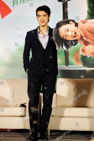 """Stock Picture of Japanese actor Takeshi Kaneshiro poses with Zhou Dongyu's portrait for press during a media event promoting his new Movie """"This Is Not What I Expected"""" in Taipei, Taiwan"""