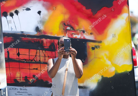 Local resident Sharon Jones takes images of the commemoration of the 25th anniversary of widespread rioting at Florence and Normandie Avenues in South Los Angeles, California, USA, 29 April 2017. This intersection was the flashpoint after the acquittal of LAPD police officers shown in a videotaped beating of black motorist Rodney King. Numerous korean-owned businesses were looted and destroyed in the rioting.