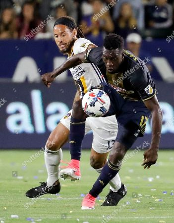 Philadelphia Union forward C.J. Sapong, right, kicks the ball away from LA Galaxy midfielder Jermaine Jones during the first half of an MLS soccer match in Carson, Calif