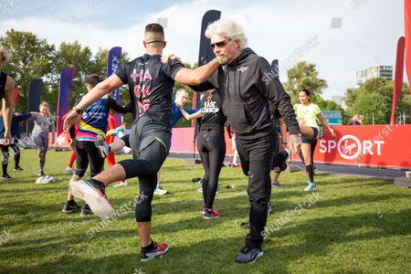 Faisal Abdalla (Go Fit Yourself trainer) and Sir Richard Branson warming up at the Virgin Sport Hackney Half Marathon