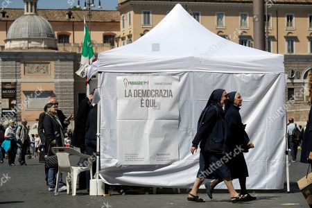 Two nuns walk past a makeshift gazebo set up around the country for the Democratic party's primary elections, in Rome . Italians are voting for a new leader of the Democratic Party in a primary expected to give Matteo Renzi a fresh mandate. Challenging him in the primary are Justice Minister Andrea Orlando and Michele Emiliano, who is governor of the southern region of Puglia