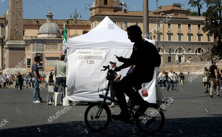 A man on a bicycle rides past a makeshift gazebo set up around the country for the Democratic party's primary elections, in Rome . Italians are voting for a new leader of the Democratic Party in a primary expected to give Matteo Renzi a fresh mandate. Challenging him in the primary are Justice Minister Andrea Orlando and Michele Emiliano, who is governor of the southern region of Puglia