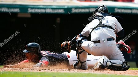 Jose Ramirez, Carlos Ruiz Cleveland Indians' Jose Ramirez, left, scores past Seattle Mariners catcher Carlos Ruiz on a sacrifice fly by Lonnie Chisenhall during the third inning in a baseball game, in Cleveland