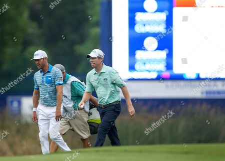 Teammates Graham DeLaet, left, and David Hearn, both of Canada, leave the course for a rain delay during the final round of the PGA Zurich Classic golf tournament's new two-man team format at TPC Louisiana in Avondale, La