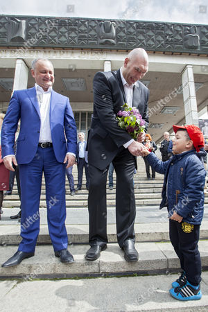 Nikolai Valuev, Russian former professional boxer (C) stays near the President of Moldova Igor Dodon (L), receives flowers from a little boy at a rally on the occasion of May Day in front of National Opera and Ballet Theatre of Moldova in Chisinau, Moldova, 01 May 2017. Labor Day or May Day is observed all over the world on the first day of May to celebrate the economic and social achievements of workers and fight for labourers rights.