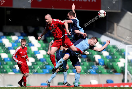 Stock Photo of Enniskillen Rangers vs Hill Street. Enniskillen player manager Michael Kerr wins a header