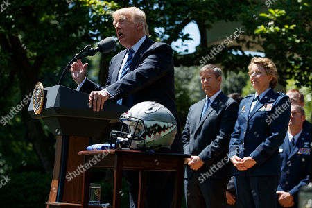 President Donald Trump speaks in the Rose Garden of the White House in Washington, during a presentation ceremony of the Commander-in-Chief trophy to the Air Force Academy football team. Air Force Academy Superintendent Lt. Gen. Michelle Johnson is at right