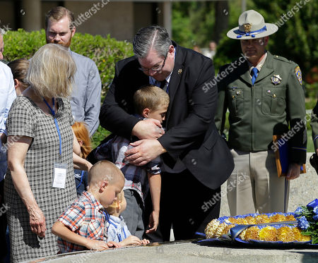 Stock Image of Preston Tayler, 9, the son of California Highway Patrol Officer Nathan Taylor, is hugged by his grandfather, Jeffery Taylor, after his father's name was added to the CHP Memorial, during ceremonies at the Highway Patrol Academy, in West Sacramento, Calif. Nathan Taylor, 35, died March 13, 2016, from injures suffered when he was struck by an SUV the day before while investigating a traffic collision on Interstate 80 in the Sierra Nevada. Also seen, from left, is Linda Taylor, Nathan's mother, and Nathan's sons Wyatt, 7, second from left, and Joshua, 4, third from left