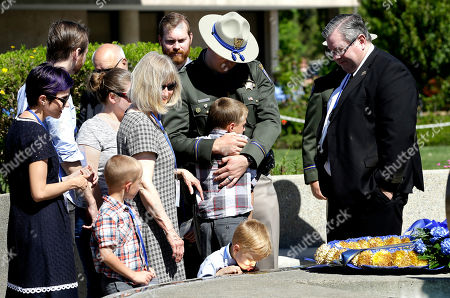 Preston Tayler, 9, the son of California Highway Patrol Officer Nathan Taylor, is hugged by his uncle, CHP Officer Stephen Taylor, after his father's name was added to the CHP Memorial, at the CHP Academy, in West Sacramento, Calif. Nathan Taylor, 35, died March 13, 2016, from injures suffered when he was struck by an SUV the day before while investigating a traffic collision on Interstate 80 in the Sierra Nevada. Also seen are Becky Taylor, left, wife of Nathan, and sons, Wyatt, 7, second from left, and Joshua, 4