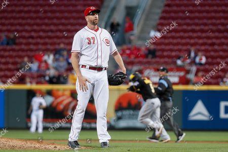 Cincinnati Reds starting pitcher Scott Feldman reacts after giving up a three-run home run to Pittsburgh Pirates' Josh Harrison, center right, in the fourth inning of a baseball game, in Cincinnati