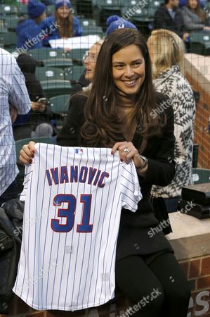 Former French Open tennis champion, Ana Ivanovic, wife of Chicago Fire soccer star Bastian Schweinsteiger, poses with her Chicago Cubs jersey before a baseball game between the Cubs and the Philadelphia Phillies, in Chicago