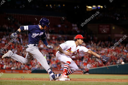 Milwaukee Brewers' Nick Franklin, left, is safe at first as St. Louis pitcher Cardinals' Carlos Martinez waits for the throw from Cardinals first baseman Matt Carpenter during the seventh inning of a baseball game, in St. Louis. Carpenter was charged with a fielding error on the play