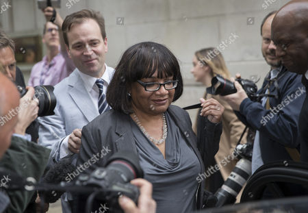 Shadow Home Secretary Diane Abbott is surrounded by reporters as she leav Milbank Studios in Westminster, with the help of Lord Prescott's son David Prescott (behind left) after an appearance on the Daily Politics program