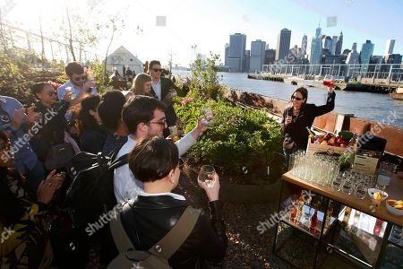 Stock Picture of Strongbow Vice President of Marketing Jessica Robinson toasts New York's first floating food forest at a garden party celebrating the partnership between Strongbow Hard Apple Ciders and Swale, in New York