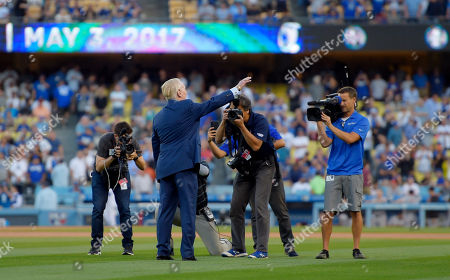 Hall of Fame broadcaster Vin Scully waves to fans after his induction into the Los Angeles Dodgers Ring of Honor prior to a baseball game between the Dodgers and the San Francisco Giants, in Los Angeles