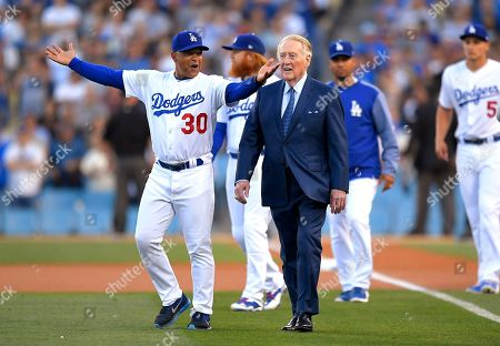 Vin Scully, Dave Roberts Broadcaster Vin Scully, right, walks onto the filed with Los Angeles Dodgers manager Dave Roberts for his induction into the Los Angeles Dodgers Ring of Honor, prior to a baseball game between the Dodgers and the San Francisco Giants, in Los Angeles