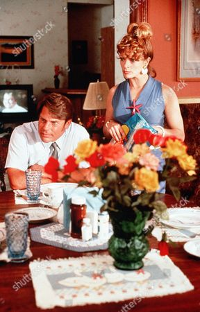 Stock Picture of 'Welcome Home, Roxy Carmichael'  Film - 1990 -  Les Bossetti (Graham Beckel) sits at the table as his wife Rochelle (Francis Fisher) stands behind