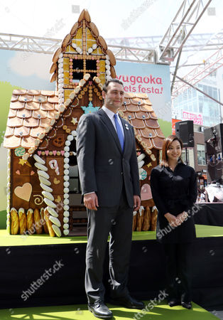 Former Bulgarian sumo champion or Ozeki Kotooshu (L) who was named as the sweet ambassador and Japanese confectionery artist Junko Tanaka (R) display a 3m tall confectionery house called 'Jiyugaoka Sweets House'
