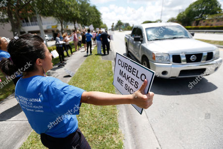 Maria Angelica Ramirez, 30, demonstrates during a health care protest outside U.S. Rep. Carlos Curbelo's offices, in Miami