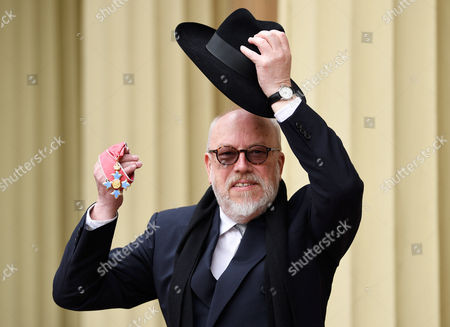 Stock Image of Political cartoonist Peter Brookes shows his CBE after the investiture service at Buckingham Palace