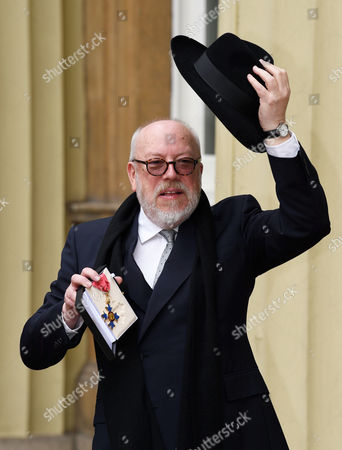 Political cartoonist Peter Brookes shows his CBE after the investiture service at Buckingham Palace