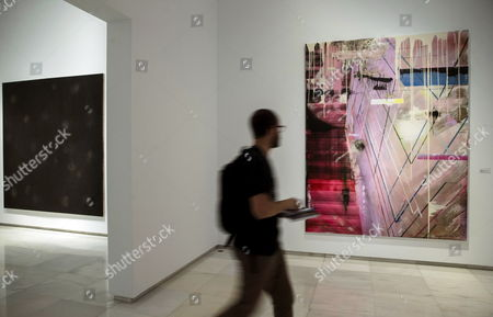 A visitor passes in front of the artworks 'MRCS847asymmetrical warfare' (L) by Mild Ceulemans and 'Passion-Passion' (R) by Marc Maet  during the presentation of the exhibition 'Painting after Postmodernism (Belgium-USA)' at the Episcopal Palace in Malaga, southern Spain, 04 May 2017 (issued on 05 May 2017). The exhibition features paintings by sixteen Belgian and US artists, including Ed Moses, Larry Poons or Paul Manes and will run from 05 May to 02 July 2017.