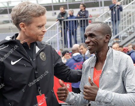 Olympic marathon champion Eliud Kipchoge, right, talks with Nike CEO and President Mark Parker, after crossing the finish line of a marathon at the Monza Formula One racetrack, Italy, . Eliud Kipchoge was 26 seconds from making history on Saturday but in the end the Olympic champion was just short of becoming the first person to run a marathon in less than two hours. Kipchoge ran the 26.2 miles (42.2 kilometers) in 2 hours and 24 seconds, beating Dennis Kimetto's world record of 2:02:57, but the Kenyan failed to run the first sub-two hour marathon