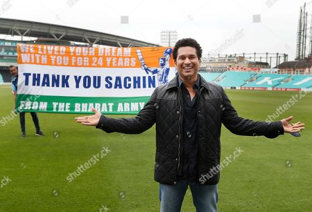 Indian former cricket player Sachin Tendulkar smiles in front of a flag held up by fans, on the pitch at the Oval cricket ground whilst promoting his upcoming film, in London, . The film, Sachin: A Billion Dreams is an Indian biographical film written and directed by James Erskine and produced by Ravi Bhagchandka. The film, based on the life of Tendulkar will be released on May 26